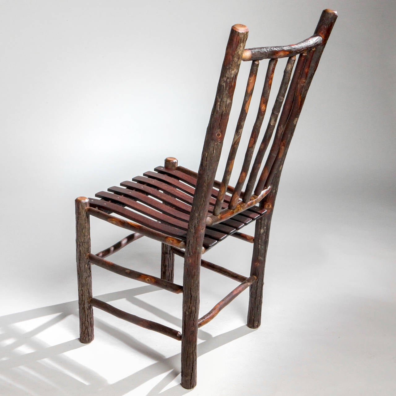 Handcrafted Adirondack hall or dining natural wood chair with spindle chair back and split wood seat.