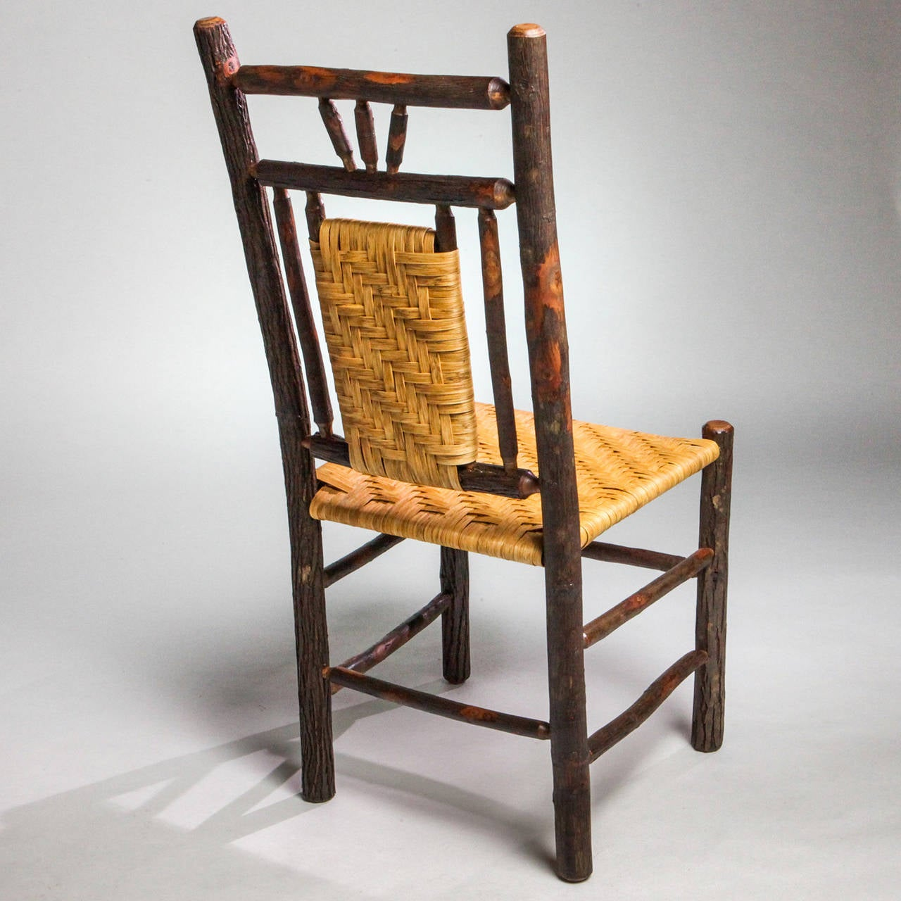 Handcrafted Adirondack hall or dining natural wood chair with woven split bark chair back and seat.
