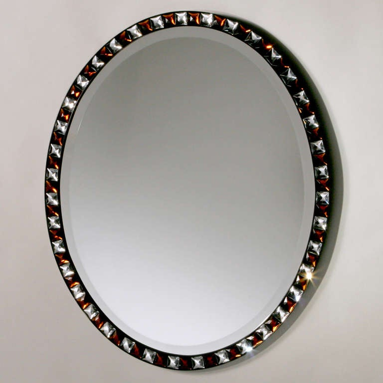 Irish oval beveled Regency style mirror with frame of cut-glass, alternating clear and smoky topaz facets. Two available. Price for each.