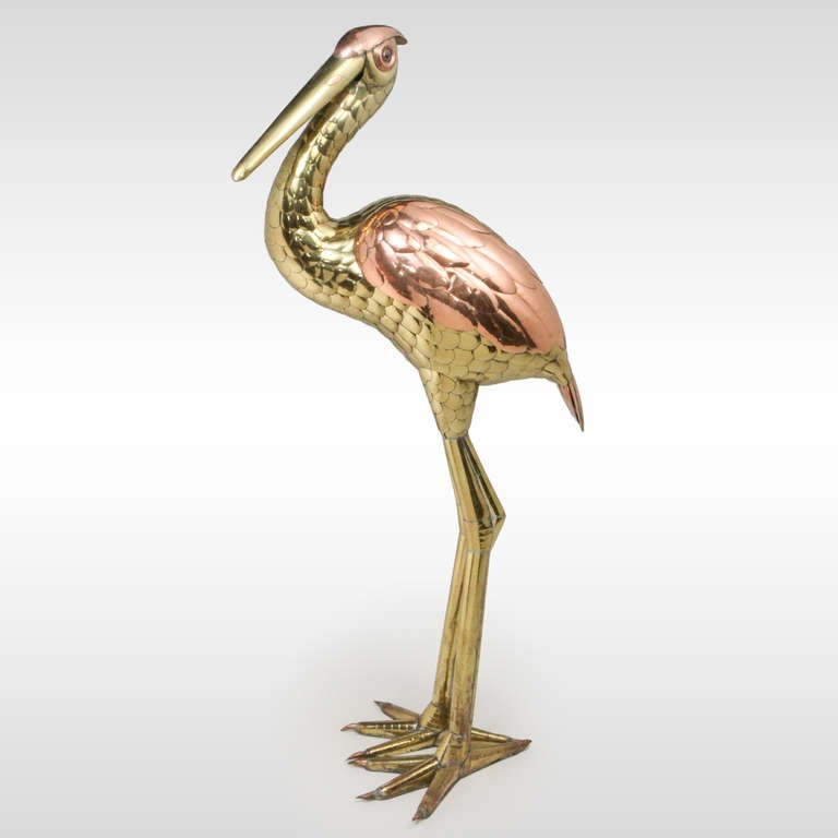 Large standing heron in brass and copper by the Mexican artist and sculptor Sergio Bustamante. This graceful heron stands almost four feet tall, with finely detailed feathered bodice. Bustamante established the
