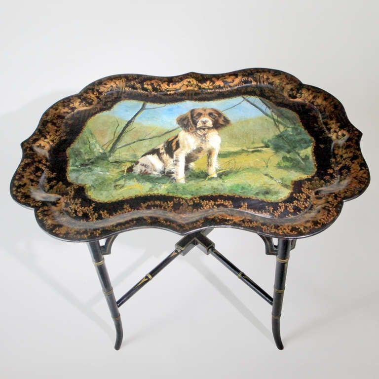 English lacquered papier-mache tray table. Large painted oval tray depicting a handsome springer spaniel dog with original beautifully patterned border. Antique tray with contemporary custom-made faux bamboo stand.