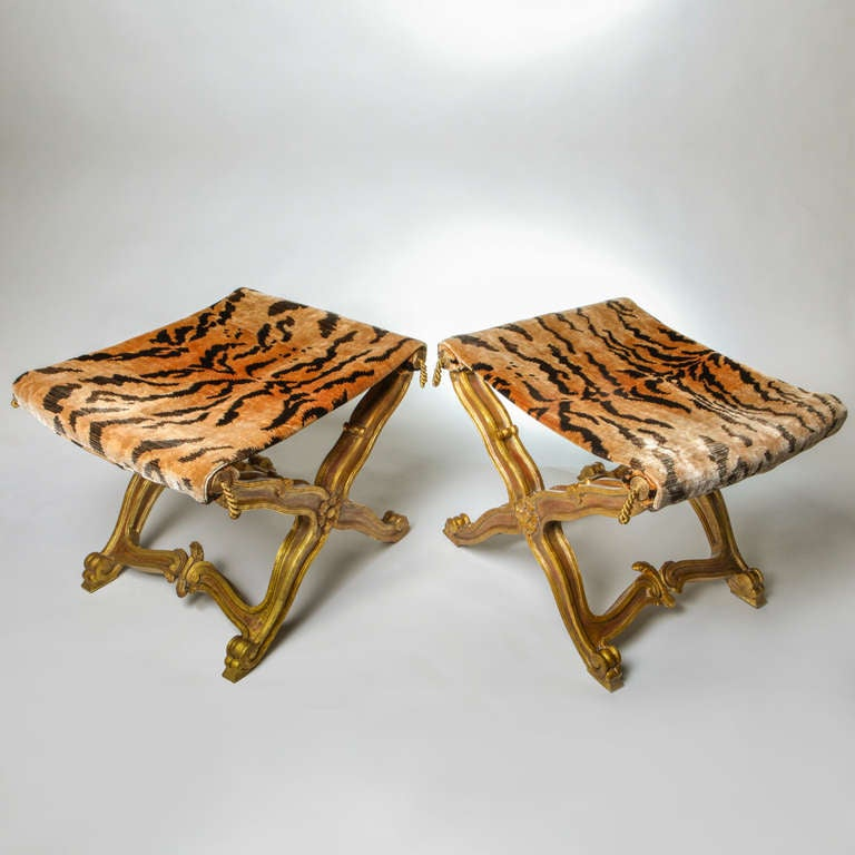 Pair of Italian scrolled and cross-legged giltwood stools with carved decorative rosettes.  Venetian animal-print silk velvet fabric seats with gold tassels.