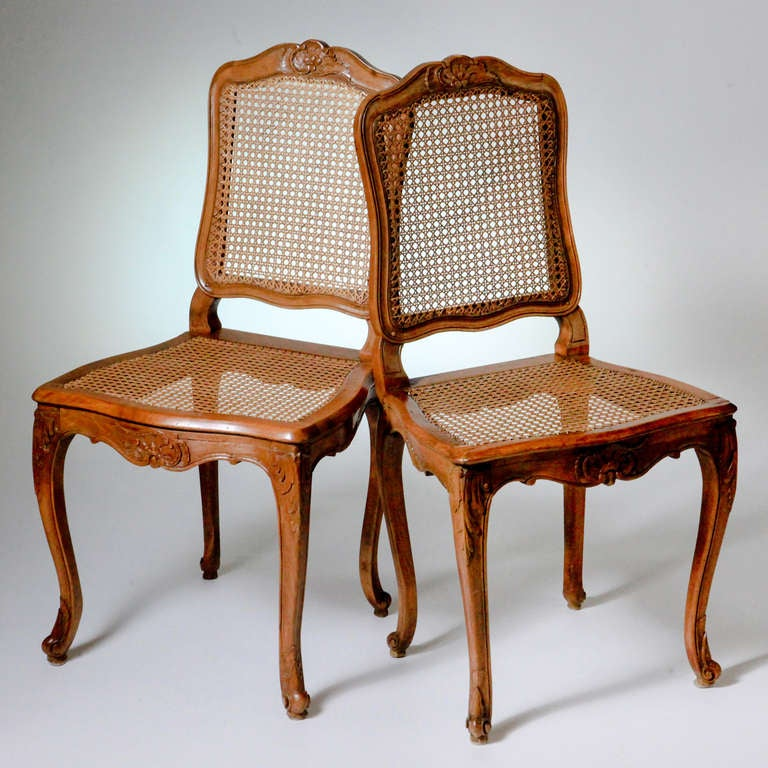 Set of two French Louis XV carved beechwood side chairs with caned backs and seats on cabriole legs. The chair front and crest rail with carved flower and scroll design. Two additional chairs available.