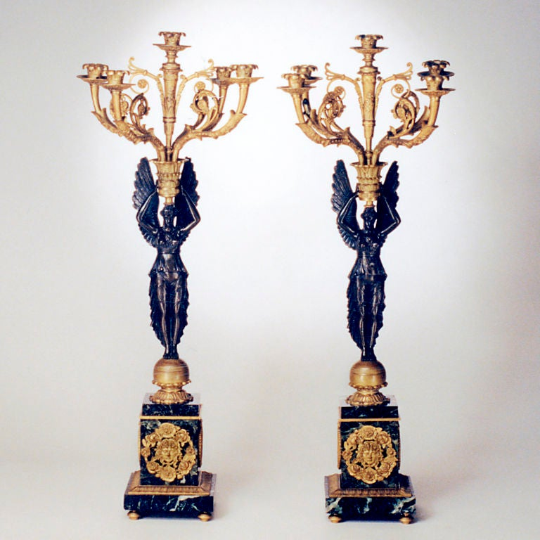 Important pair of French Empire-style five-light bronze candelabra. Each richly patinated winged victory figure rests on a serpentine base with gilt bronze mounts and holds an elaborate gilt bronze candelabrum.