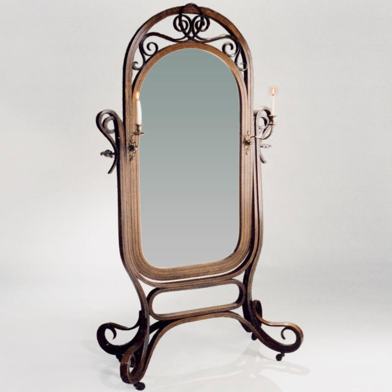 Large bentwood cheval standing mirror with attached metal candleholders. Gracefully scrolled legs and top piece balance beveled oval looking glass.