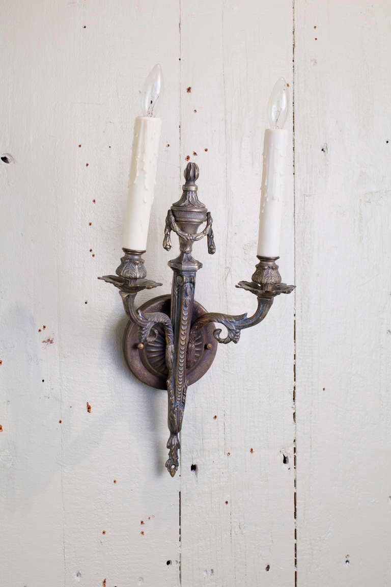 Beautiful pair of Empire-style bronze sconces from France, circa 1910.  Features an urn with swag motif with a beautiful patina and excellent detailed casting. Newly wired in the US with two candelabra sockets and all UL listed parts. Choice of