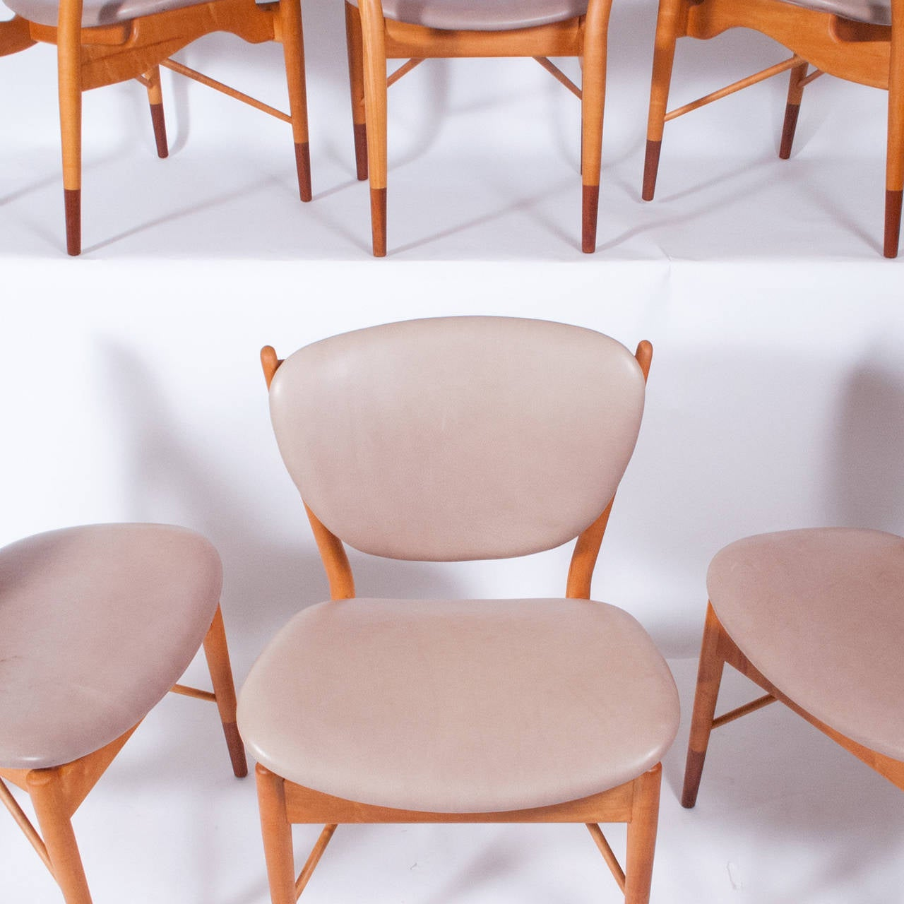 Six side chairs, floating back and seat with two support stretchers. Sycamore and Italian walnut with previously reupholstered seat and back in light gray leather . A Fine example of Finn Juhl's organic design. Made by Baker.