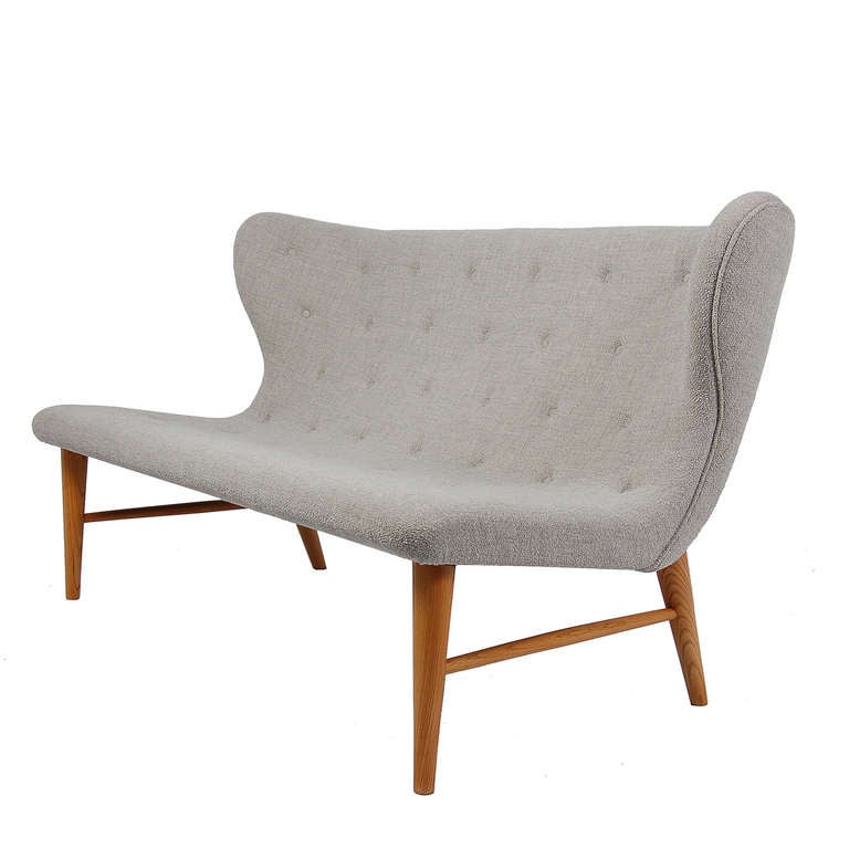 Elegant settee, with curved form, reupholstered with Kvadrat fabric, having buttoned seating on elmwood legs. Original design from Nordiska Kompaniet, Sweden.