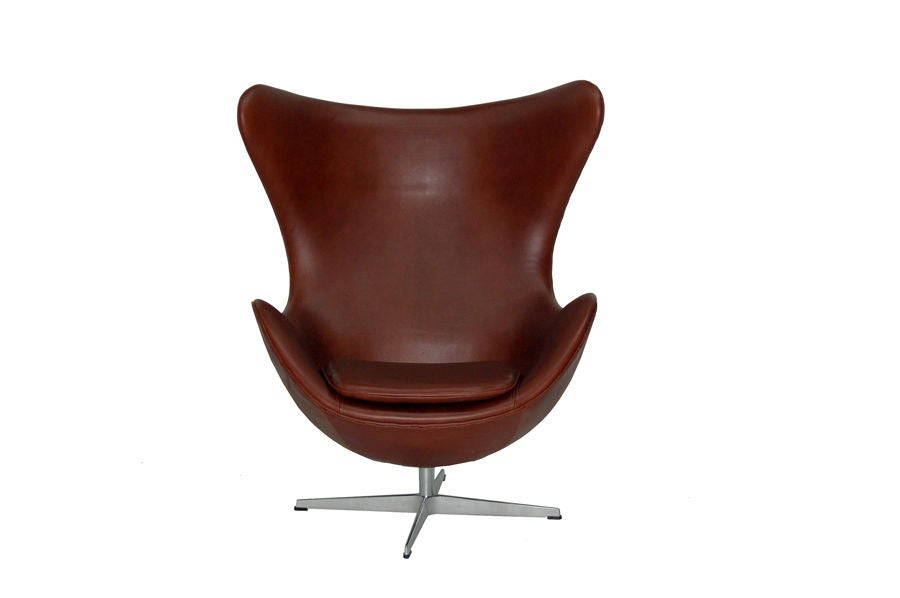 Iconic classic by Jacobsen, this is an early model that has been reupholstered in dark, reddish-brown leather. Aluminum swiveling base. Made by Fritz Hansen.