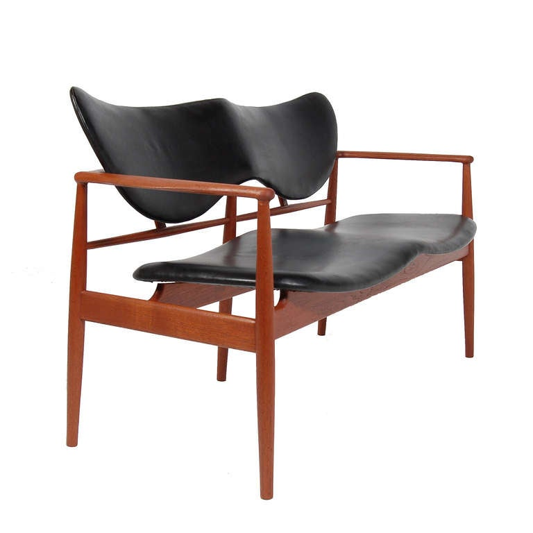 Important and early production Juhl design, rarely found. Solid teak sculptured frame with heart-shaped floating back and seat. Original leather. Handmade by Niels Vodder. Signed.