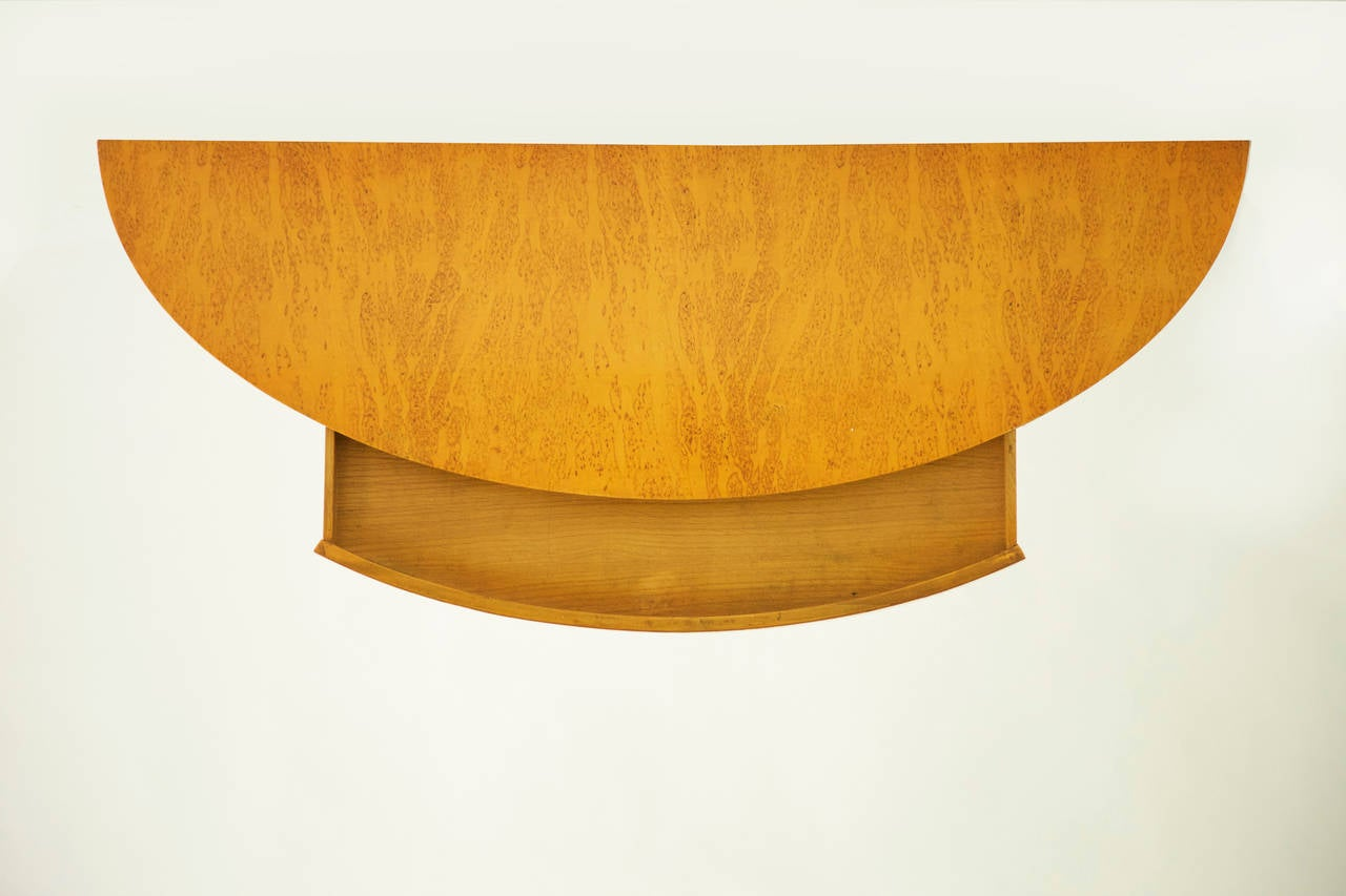A wall-mounted floating shelf with pull-out drawer, model no. 4905. Finished with a birch burl veneer. In the last image, a smaller version, model no. 4903 is displayed on the right of this shelf, also available separately.