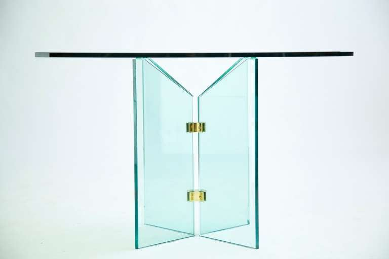 A square beveled piece of glass rests on a four point base held together by two brass brackets.