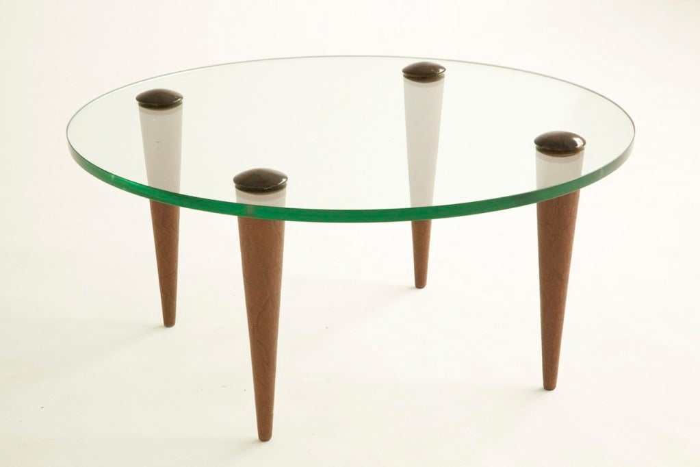 Gilbert Rohde cocktail table for Herman Miller. Tapered spiked legs pass through glass with wood domed covered caps.