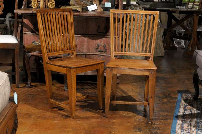 A set of eight Swedish Gustavian period late 18th century side stick-back heart of pine country chairs. Each chair features an openwork trapezoid back gently leading to eye to a simply shaped wooden seat. Raised on four tapered legs, the chairs are