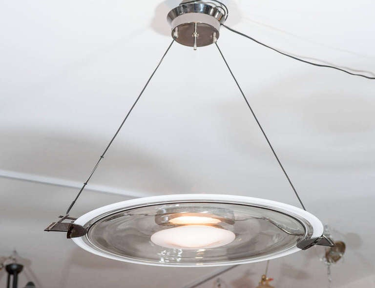 A special single smoked glass disc with white center is illuminated from above by a halogen bulb.