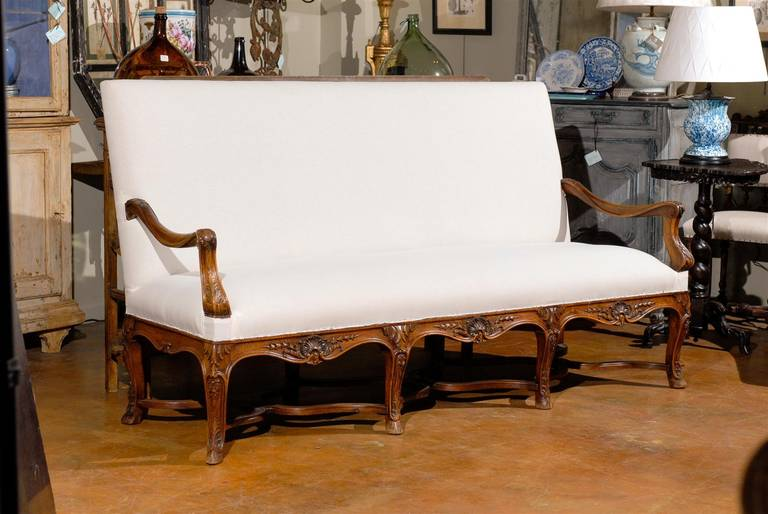 19th century Louis XV style French carved walnut canape, the rectangular back and conforming bench seat upholstered in white muslin, with a carved apron and raised on eight cabriole legs joined a single warped stretcher.
