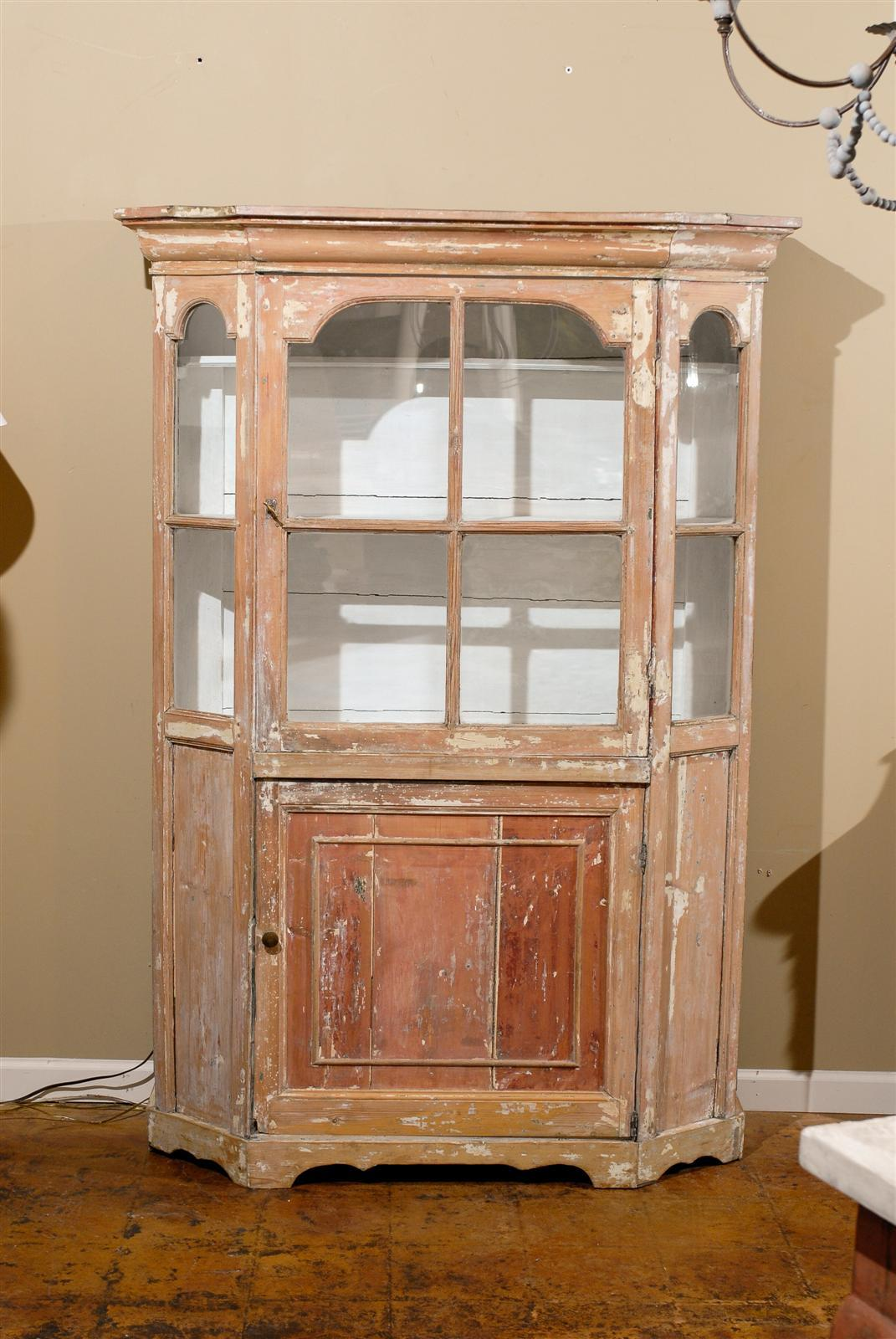 This Dutch curio cabinet from the mid-19th century features a cornice over two pairs of doors placed above each other. The piece is visually separated into two sections: the upper section, made of glass, is the vitrine. The central door, with its