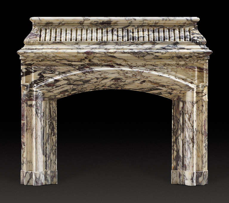 Antique William IV breche Violette marble fireplace mantel with heavily moulded shelf, the frieze of convex shape with deep vertical fluted mouldings. The jambs of bolection form, the opening with arched header, the whole raised on foot blocks.