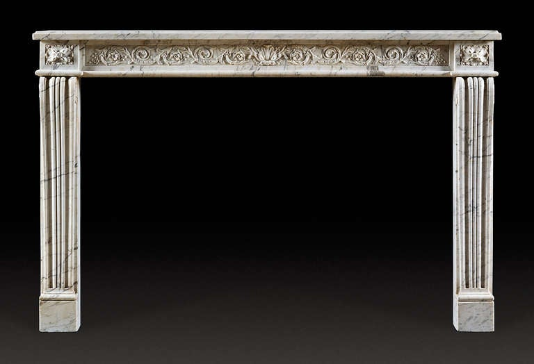 In veined statuary marble with typical straight lines and symmetrical sculptured decoration, French, 18th century. With rectangular moulded shelf above the frieze which is carved with scrolling, flowering acanthus. The jambs in the form of tapering