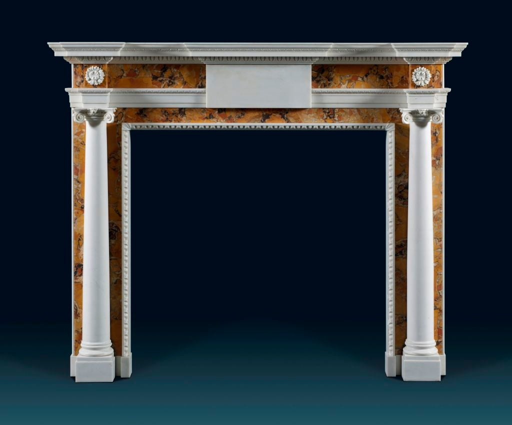 Description: Modelled on a well proportioned mid-18th century Anglo-Irish original, this Sienna and white marble chimneypiece features a moulded breakfront shelf with egg and dart decoration above a frieze centred with a plain white marble tablet.