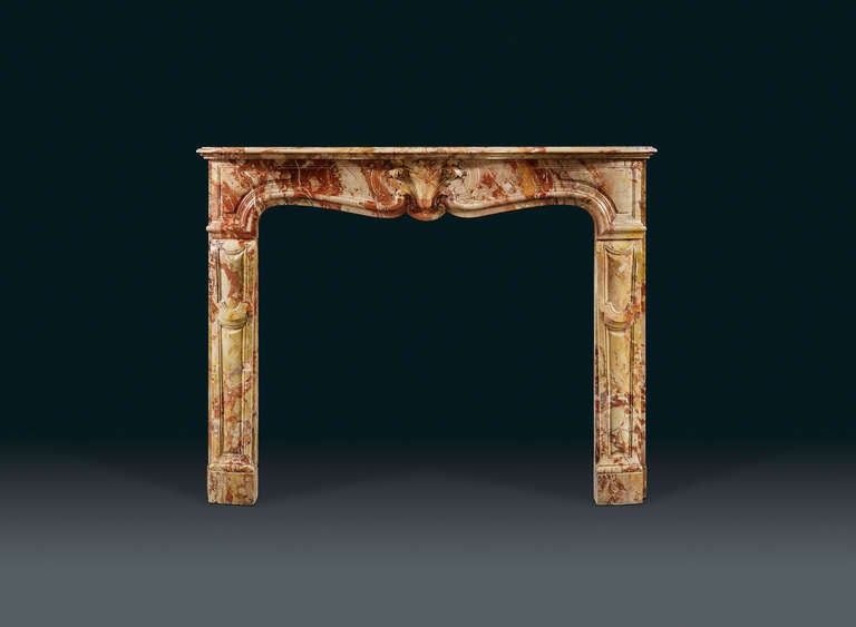 An attractive, Louis XV (1715-1774) style and period, Sarrancolin marble chimney piece of superb color, with serpentine shelf and frieze, which is centered with a well sculpted acanthus leaf, upheld by a Rococo C-scroll. The console shaped jambs