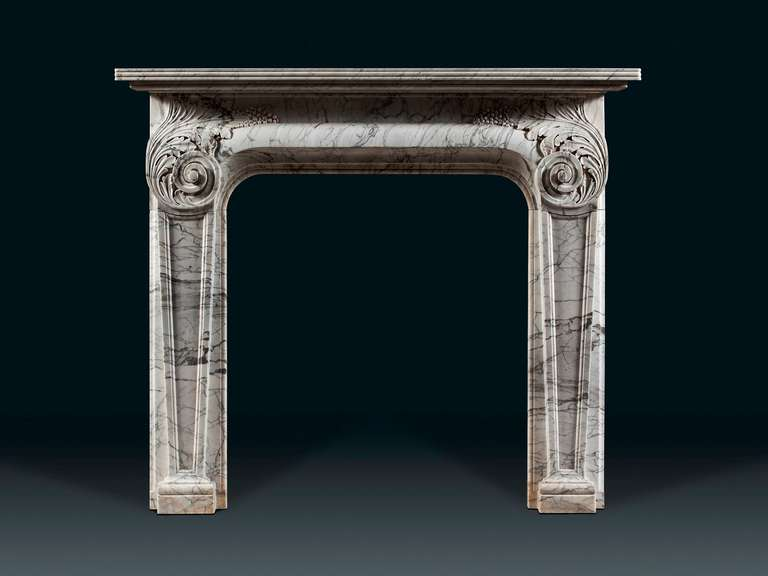 Carved in veined streaked Carrara marble, the moulded shelf with ribbed edge above the ogee barrel-shaped frieze. The jambs in the form of tapering, inverted obelisks capped with wonderful acanthus, which grows from deep and tight scrolls and