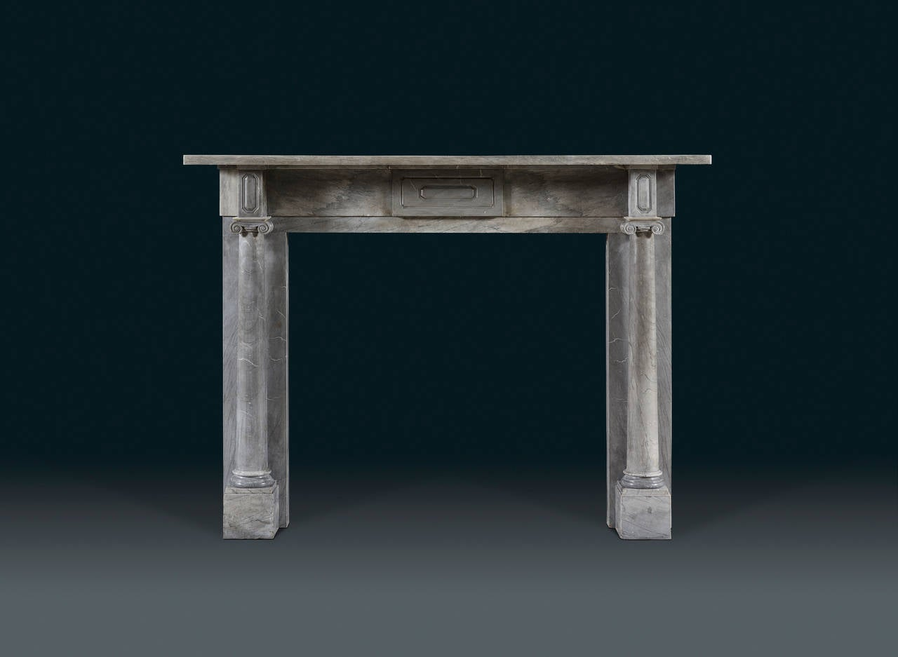 in Bardiglio marble, with rectangular shelf above a plain frieze with a tablet carved with geometric decoration. The jambs with tapering Ionic full rounded columns surmounted with blockings decorated with designs echoing the centre of the frieze.