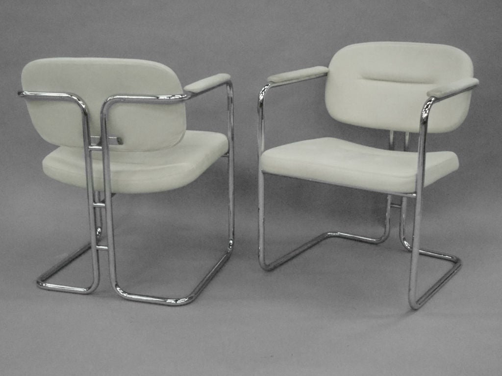 white leather dining chairs on chrome frame by dux company