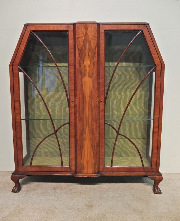 """An Art Deco cabinet in mahogany, with crotch of mahogany center panel. Two glass shelves are situated behind doors of arched individual paned glass. The clearance from the top shelf to the top of the piece is: 10 3/4"""", middle shelf to top shelf: 15"""