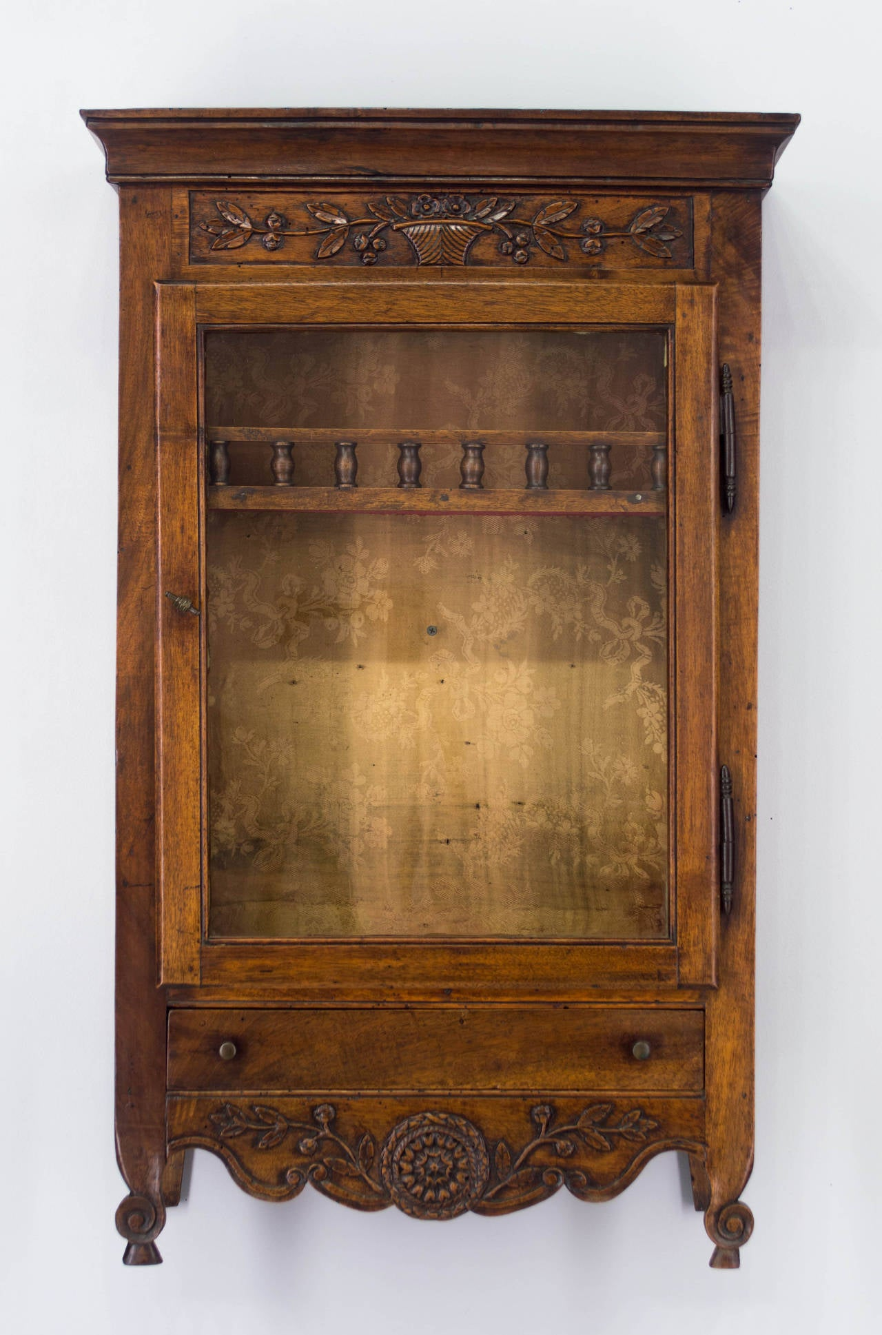 An 18th century Provençal walnut verrio, or display cabinet, with a glass door and and a dovetailed drawer. Beautiful hand-carved floral decoration. Interior is lined with fabric and has one shelf with a railing. Original brass hardware and glass