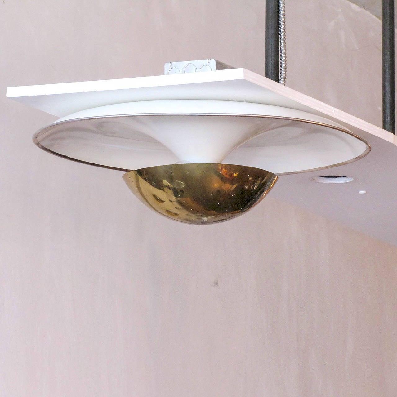 Wonderful flush mount ceiling fixture by Gino Sarfatti for Arteluce, large organically shaped ivory enameled reflector with perforated brass shade, three bulb setup.