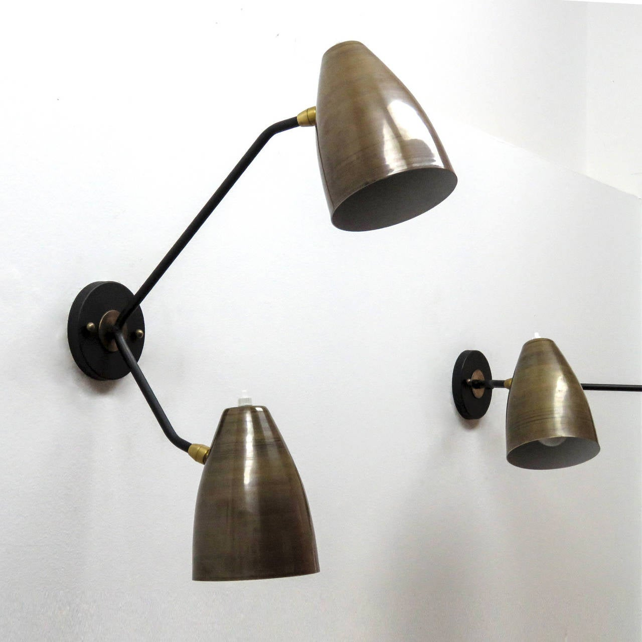 Wonderful asymmetrical double arm wall lights, two fully adjustable raw brass shades with white enameled interiors on black enameled arms, can be mounted vertically or horizontally, each shade with individual on and off switch.
