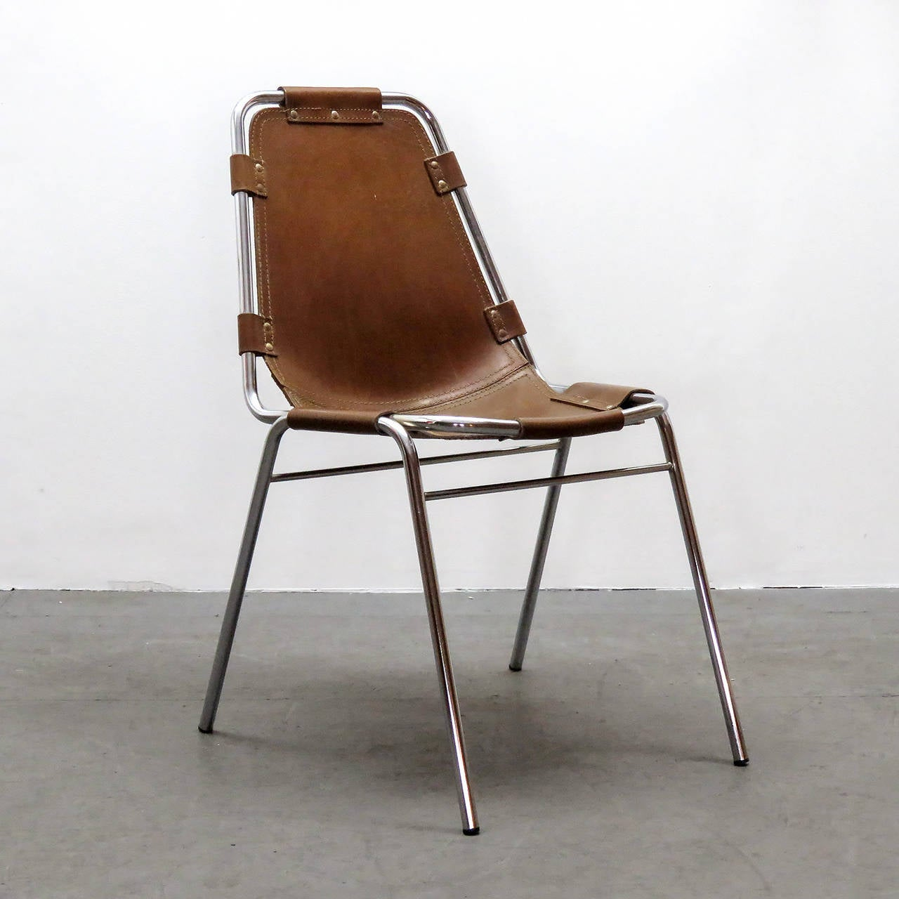 Iconic leather and metal side chair by Charlotte Perriand for the Ski resort Les Arcs in 1960, with chrome tubular frame in great condition and high quality thick leather seat with a fantastic patina to the leather.