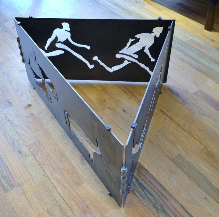 A torch cut steel coffee table featuring running figures and long horn cattle.