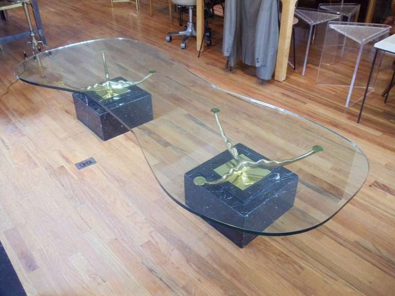 An Italian brass glass and marble coffee table by Stone International. The brass base is reminiscent of the work of Anish Kapoor. The glass top is by far the largest that we have ever offered.