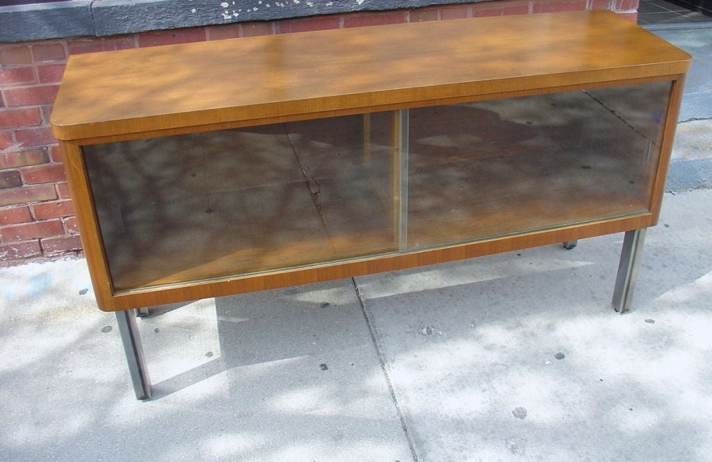 A walnut Stow & Davis credenza with a sliding glass front. The metal legs are not original to the piece.
