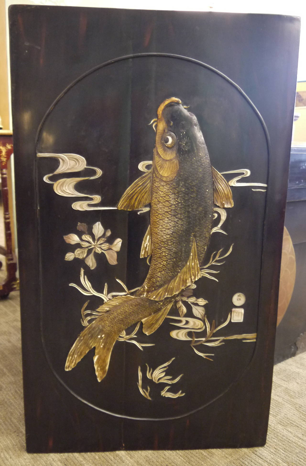 A 19th century wooden and lacquered panel, with hand-carved raised design of large carp, water, and flowers.
