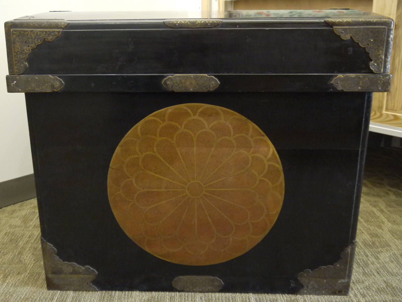 A stunning, decorative and useful antique Japanese storage trunk, with handles, metal hardware and gold crests on all sides.  The lid is removable.  The top has a very slight curve. It is not perfectly flat.