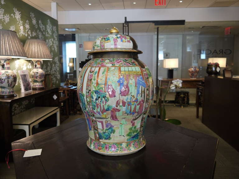 A beautiful and very large early 19th century Famille Rose temple jar, with lid and metal hardware. The design is very finely painted and features landscape and figure design in panels, with intricate borders.