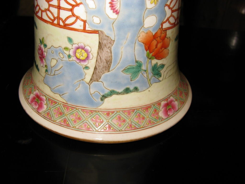 Pretty and large antique Chinese beaker shaped vase.  8.5 inches at top and 5 inches at middle.    Famille rose palette, with design of blooming peonies, fence, and exotic birds.     Intricate borders.