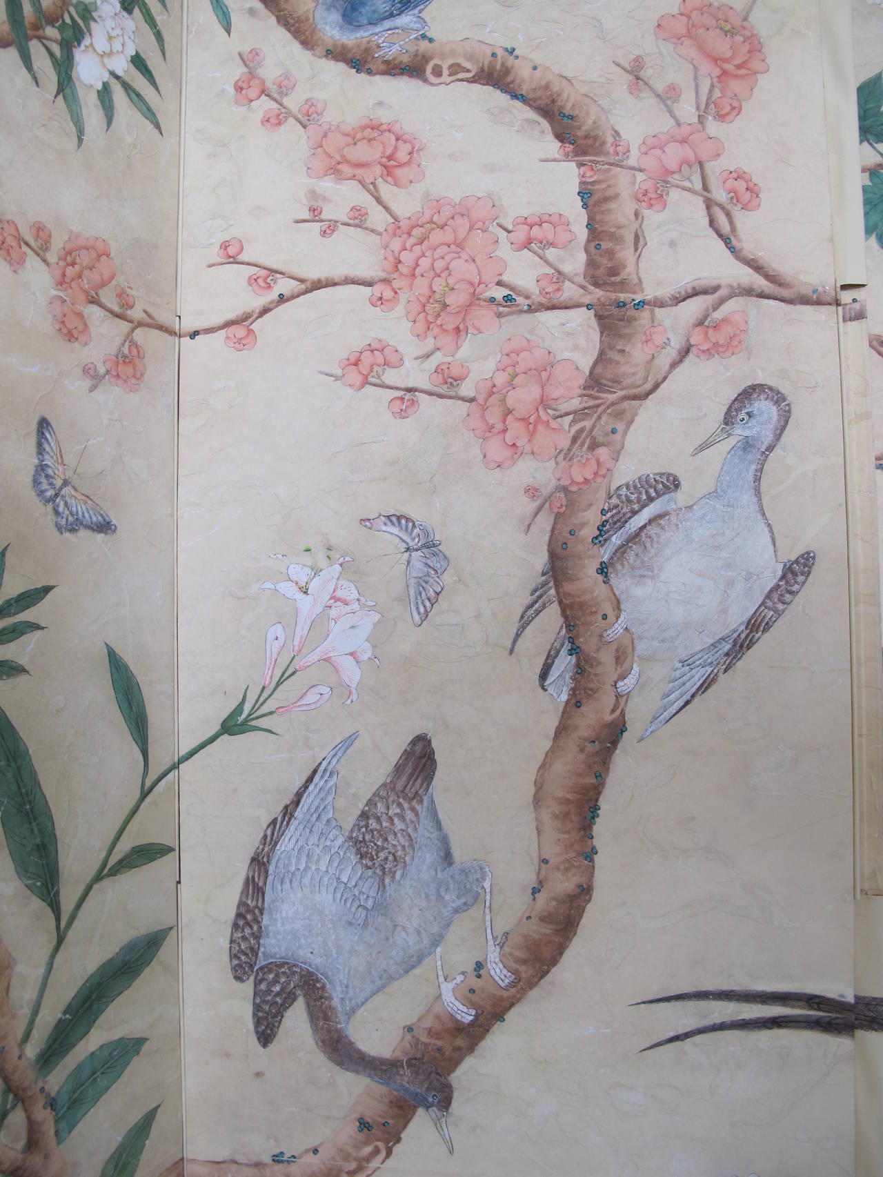 A four-panel screen with hand-painted 18th century style wallpaper applied on each panel. The design features brightly colored flowering trees, birds and butterflies. The screen has been intentionally antiqued to create the patina of an antique