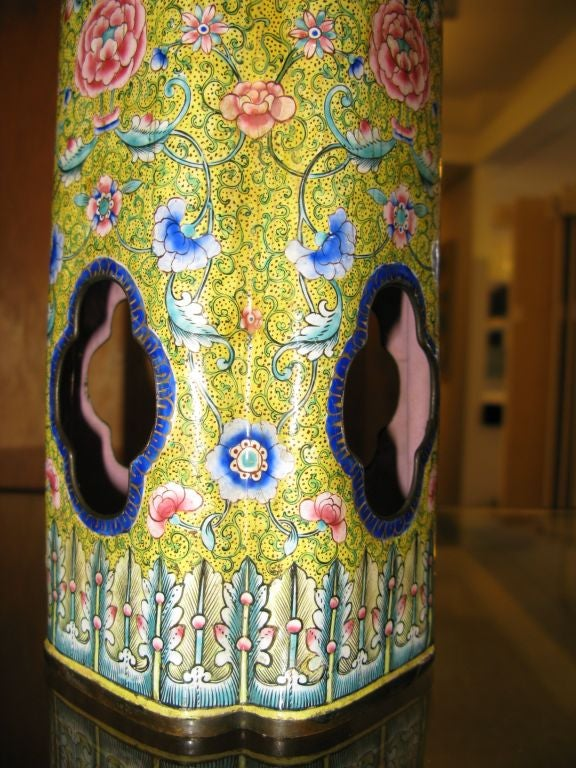 A very fine antique Chinese enamel vase with yellow background, intricate floral and vine design and open reserves borders in cobalt blue.  Pink interior.  Border of stylized feathers at base.