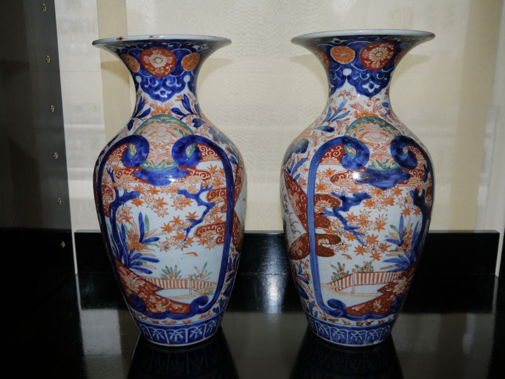 A large pair of Japanese Imari vases, with vibrant cobalt blue, orange and turquoise. With design om reserves of fence, water and