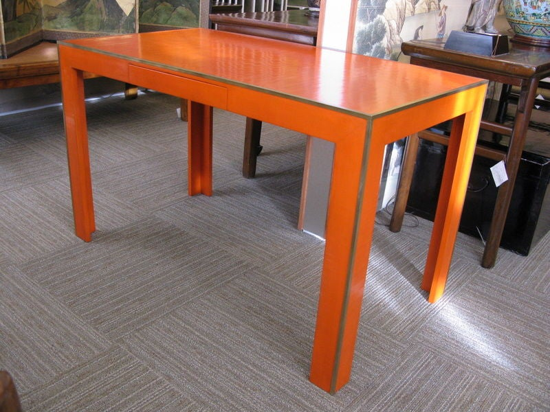 A vibrant orange lacquer desk, with crackled cashew lacquer finish, drawer in apron, straight legs, and metal edges.  Made in Gracie's studio in New York, this desk is made to order. Any color and different styles may be made to order.