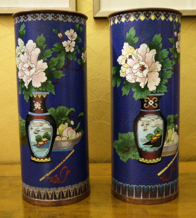A pair of Chinese cylindrical cloisonne vases with cobalt blue background, and design of vases and flowers.