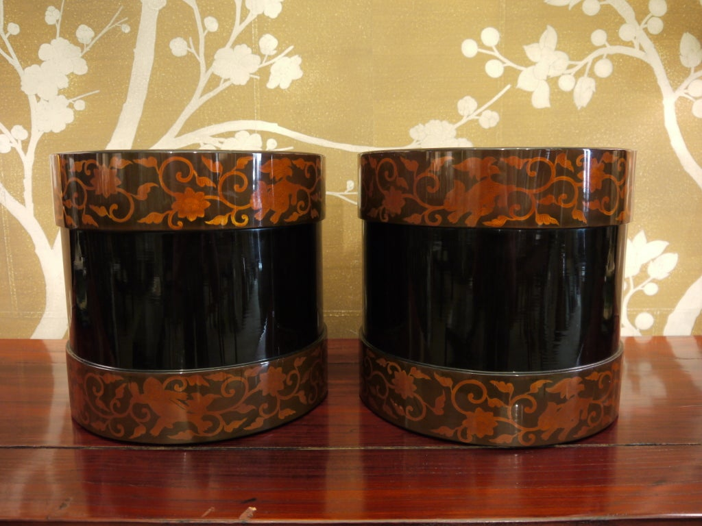 A pair of Japanese black lacquer hibachi, Meiji Period (1868-1912), with brown borders at top and base featuring design of flowers, vines and shi shi dogs.