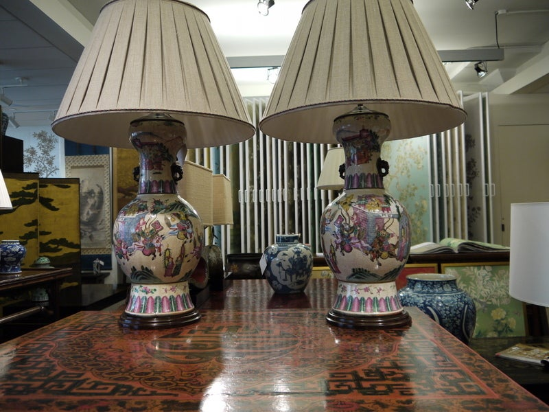 Pair of Chinese, bottle shaped vases with design of warriors, with intricate borders of leaf design.  Mounted as lamps.  Vase only - 22 inches high  Overall lamp height - 36 inches high  Widest part of vase is 10.5 inches  Shade is 24 inches in