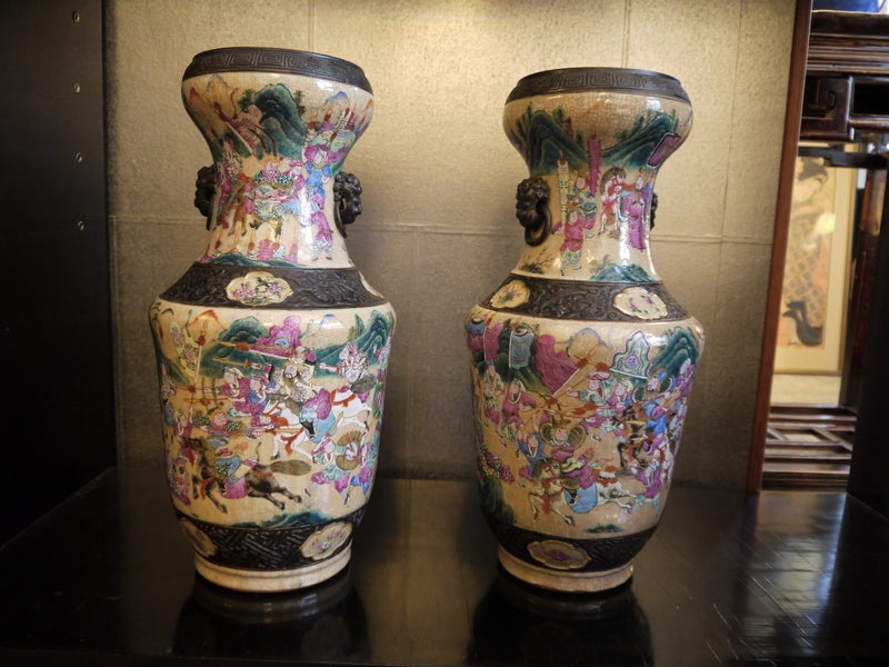 A pair of Chinese antique crackleware vases with faux bronze bands and scenes of warriors on horseback in tones of blue, pink, green and brown.