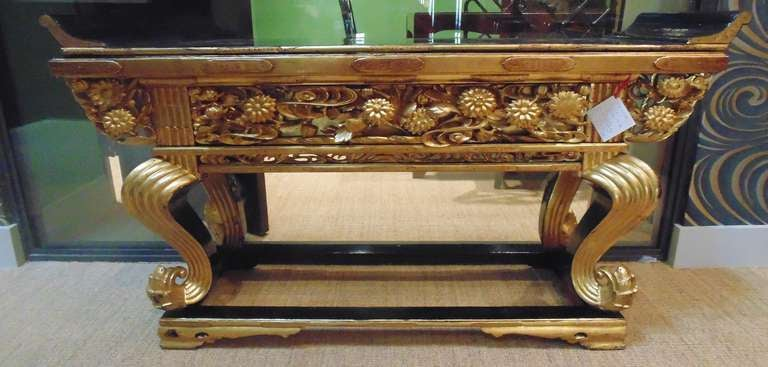 A beautiful and intricately detailed Japanese Buddhist altar table.  Meiji Period (1868-1912).  This table has a black lacquer finish on the top, with an onrnately carved and gilded apron and legs and metal hardware mounted in several areas on