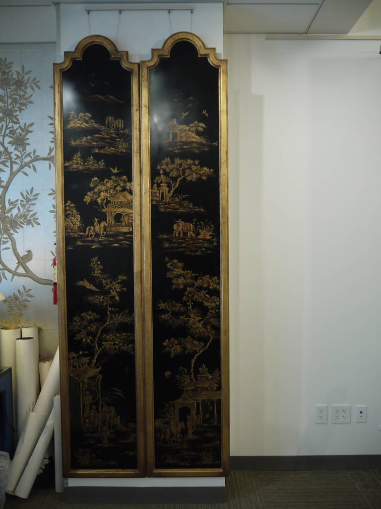 A pair of black lacquer wall panels with gold landscape design, mounted with gold frames.
